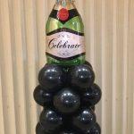 champagne bottle atop mini balloon column